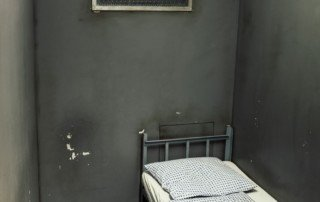 Empty Prison Bed in Cell by Camilo Jimenez